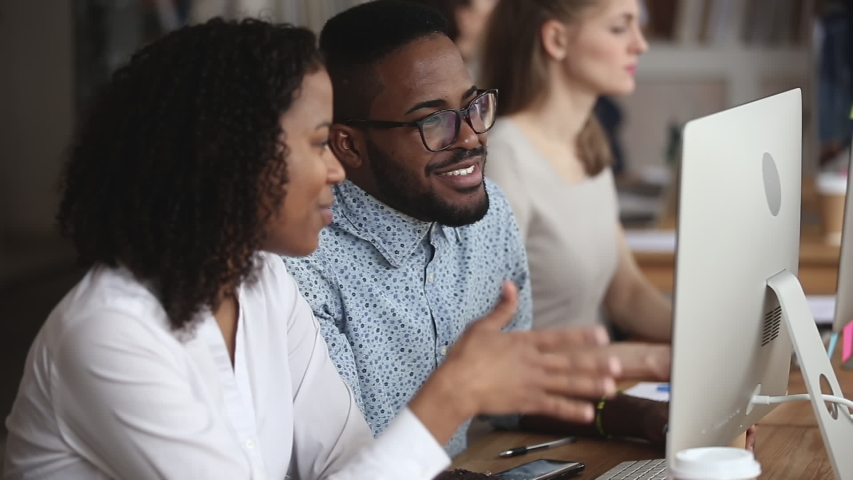 Two happy friendly african american coworkers team discuss digital online project use computer at workplace, male and female black colleagues talking working together on pc at meeting in office    Shutterstock HD Video #1034217821