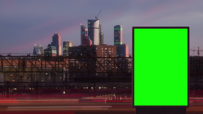 Modern billboard with a green screen on a busy highway with traffic, skyscrapers on background, timelapse of traffic at night, Moscow, Russia