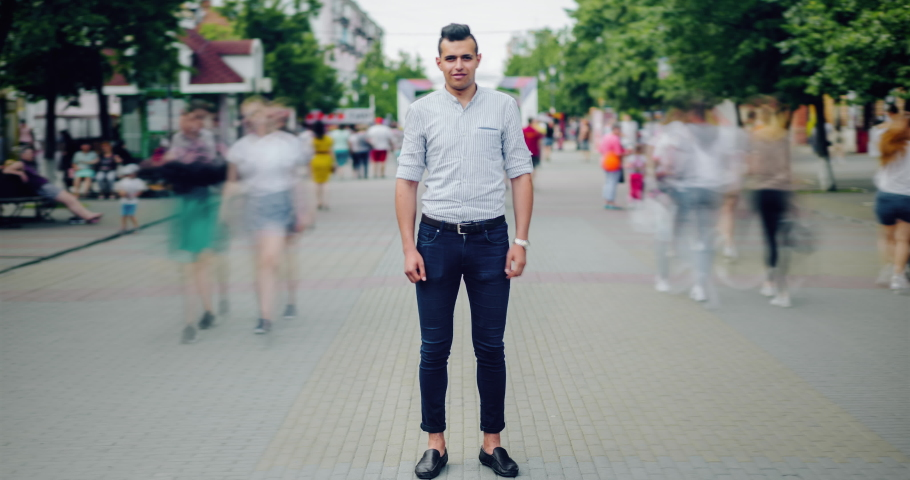 Time lapse portrait of handsome Arabian man in casual clothing outdoors in city street standing alone with serious face looking at camera while people moving around.