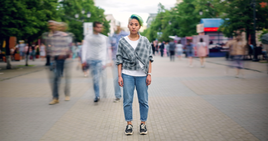 Zoom in time lapse of pretty Asian teenager looking at camera with serious face standing outdoors in pedestrian street among flow of people. Life and youth concept. | Shutterstock HD Video #1034434751