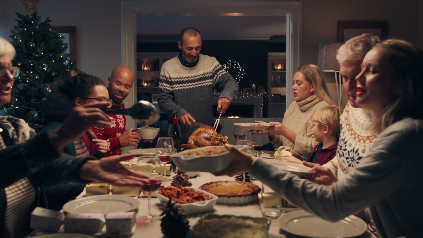 Family christmas dinner man cutting turkey serving delicious meal at festive celebration people sitting at table enjoying delicious feast celebrating holiday at home 4k footage | Shutterstock HD Video #1034496311