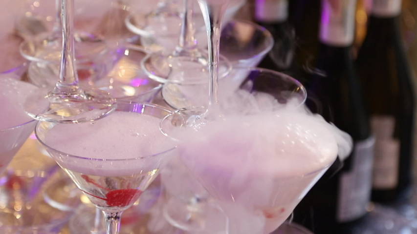 Champagne is poured into a pyramid of wine glasses with cherry bubbles and smoke | Shutterstock HD Video #1034506361