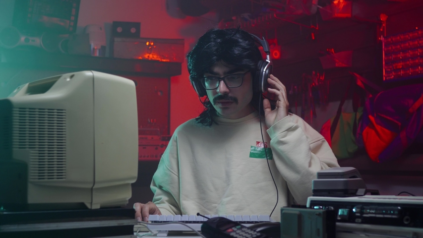 Guy from the '80s or '90s listening music in front of his old computer screen. Retro scene with vintage colors and atmosphere. | Shutterstock HD Video #1034714321