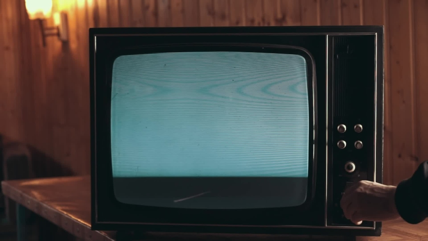 Male hand changing the channels on the Old Television. An electrical appliance with interference, old TVs are working badly. TV noise | Shutterstock HD Video #1034718341
