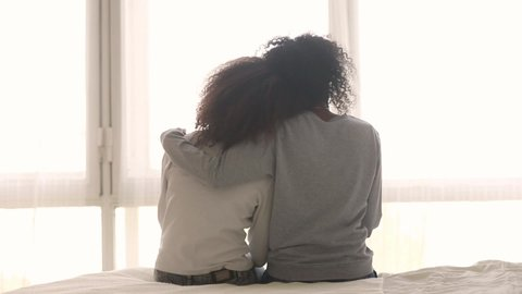 Tender moment mixed race mom teen daughter sit on bed embracing showing love, race and protection rear view. Different ages females younger elder sisters heart-to-heart talk feeling connection concept