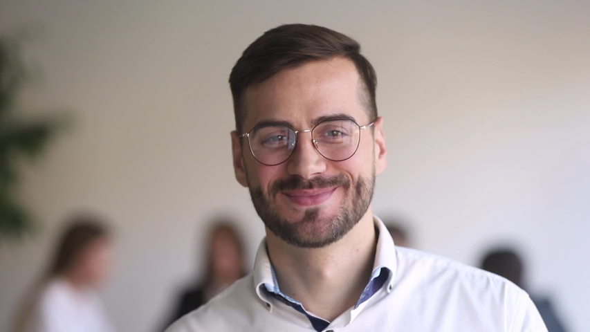 Head shot portrait leader of team handsome businessman in eyeglasses standing in office smile looking at camera. Motivation leadership, career growth, successful company member startup project concept