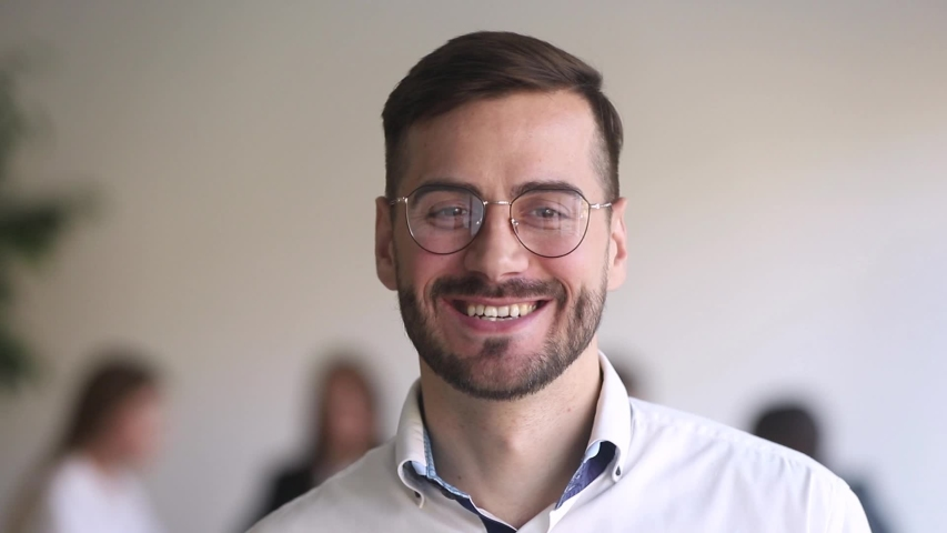 Head shot portrait leader of team handsome businessman in eyeglasses standing in office smile looking at camera. Motivation leadership, career growth, successful company member startup project concept | Shutterstock HD Video #1034756231