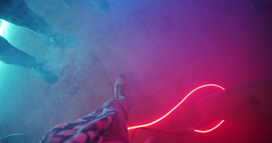 First-person view young man walking on the dance floor among his cheerful friends. Top view friendly people feet dancing together into music in nightclub. Colorful neon illumination interior. | Shutterstock HD Video #1034782091