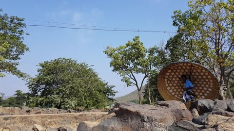 Hogenakkal , Tamilnadu / India - 12 22 2018: Hogenakkal, Tamilnadu, India - 22-Dec-2018: A man carrying a coracle and a paddle and walking on a bright sunny day with the sky and trees in the background