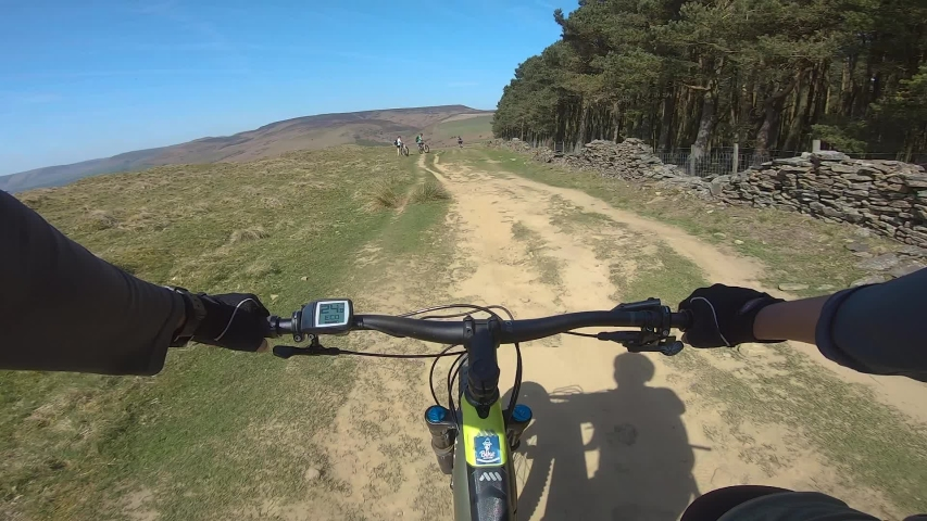 Peak District National Park / United Kingdom (UK) - 04 20 2019: POV cyclist on E Mountain Bike cycling on dirt trail riding other cyclists in the Peak District, UK during Easter Weekend, April 2019