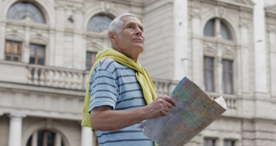 Senior male tourist exploring town with a map in hands and looking for the route while traveling in Lviv, Ukraine. A man in t-shirt and sweater that is tied around his neck. Vacation concept | Shutterstock HD Video #1034817671