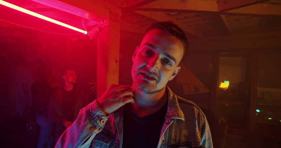 Indoor portrait of attractive blonde guy partying with friends in the club. Cool stylish guy talking on camera scratching his neck staying at the celebration party. Neon disco lights.