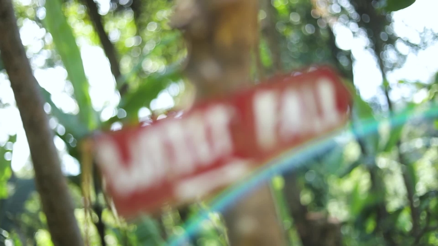 Slow Motion shot of a sign coming into focus that says WATERFALL with an arrow pointing down the trail. The sign was posted on a tree in the jungle in Bali, Indonesia. | Shutterstock HD Video #1034958521