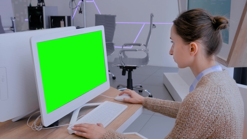 Woman looking at white monitor of desktop computer with blank green display in modern futuristic office interior. Mock up, copyspace, workspace, chroma key, template, green screen, technology concept   Shutterstock HD Video #1035027791