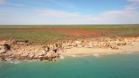 Scenic panning panoramic aerial drone view of flight high above ocean and remote beach in Western Australia, with rocky cliff coastline, summer sunny blue sky and horizon as background and copy space.