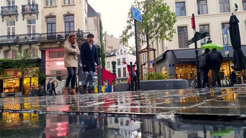 Brussels, Belgium - July 3, 2019: City street under rain with cars and people and reflection. Bad weather in Brussels, capital of Europe.