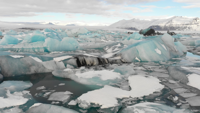 Aerial view flying over stunning icebergs floating in Jokulsarlon lagoon, dramatic natural Winter landscape (and powerful message of climate change) in Iceland  | Shutterstock HD Video #1035087881