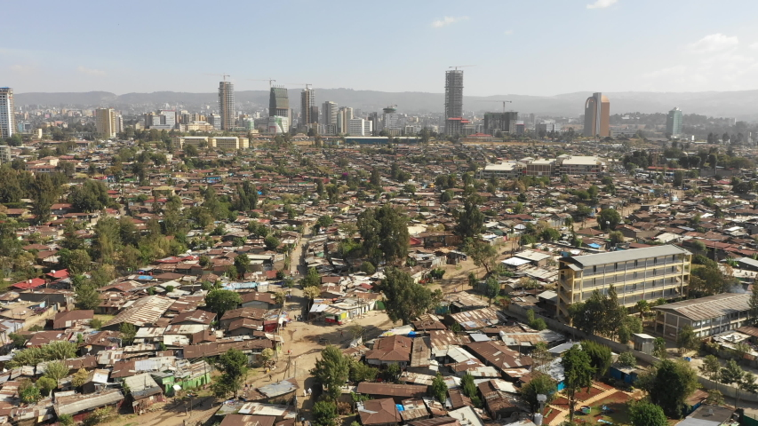 Flying over poor residential neighborhoods with rooftops made of corrugated sheet, contrast with looming modern skyline of Addis Ababa, urban development in Ethiopia Africa | Shutterstock HD Video #1035157211