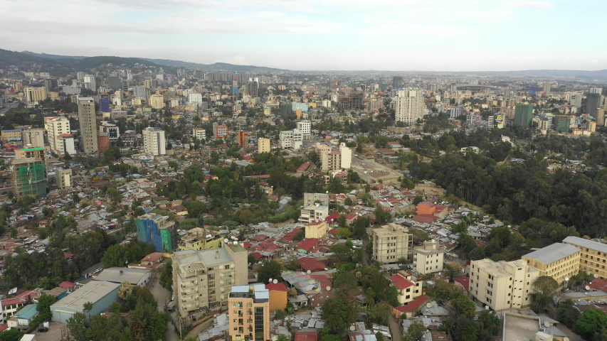 Retreating aerial footage flying over residential neighborhood in Addis Ababa, with tree filled streets and various types of homes, capital city of Ethiopia   | Shutterstock HD Video #1035157331