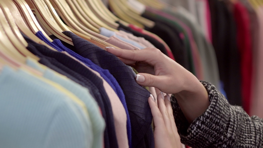 Close-up of female hands plucked a hanger with clothes. Woman's hands run across a rack of clothes. Dolly shot from the side. Woman's hand smoothing a colorful clothes. Close-up: a hanger for clothing | Shutterstock HD Video #1035197171