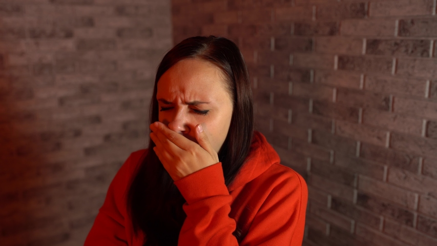 A beautiful young woman in a red hoodie yawns from fatigue on a brick background.   Shutterstock HD Video #1035215171