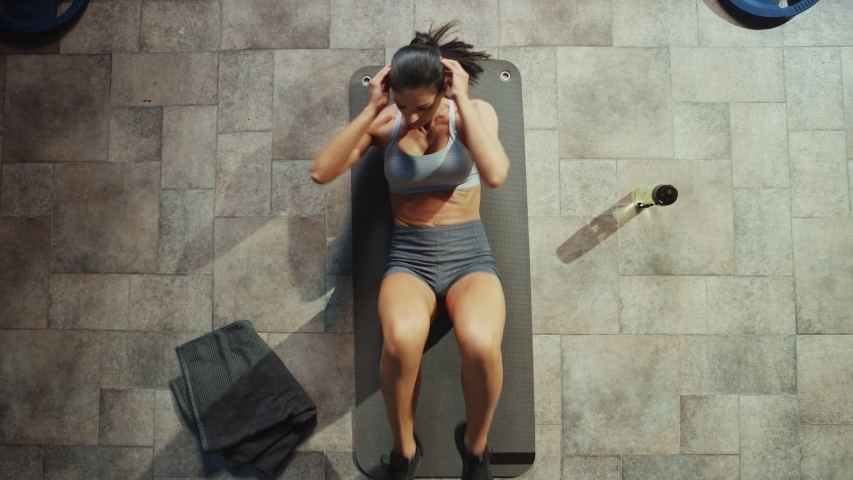 Top View of Professional Female Bodybuilder Doing Bicycle Crunches while Lying on the Yoga Mat in the Hardcore Gym. Muscular and Athletic Beautiful Woman Muscle, Power and Cardio Workout. Zoom Out | Shutterstock HD Video #1035217721