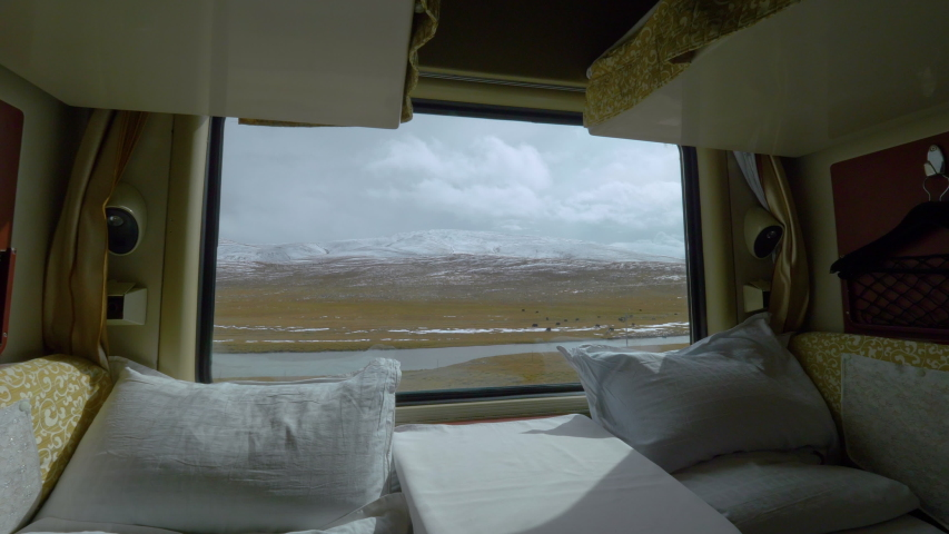 CLOSE UP: Scenic shot of the vast Tibetan plains and river through the window of an overnight train. Spectacular view of beautiful Himalaya in the distance from the comfort of private sleeping cabin. | Shutterstock HD Video #1035233501