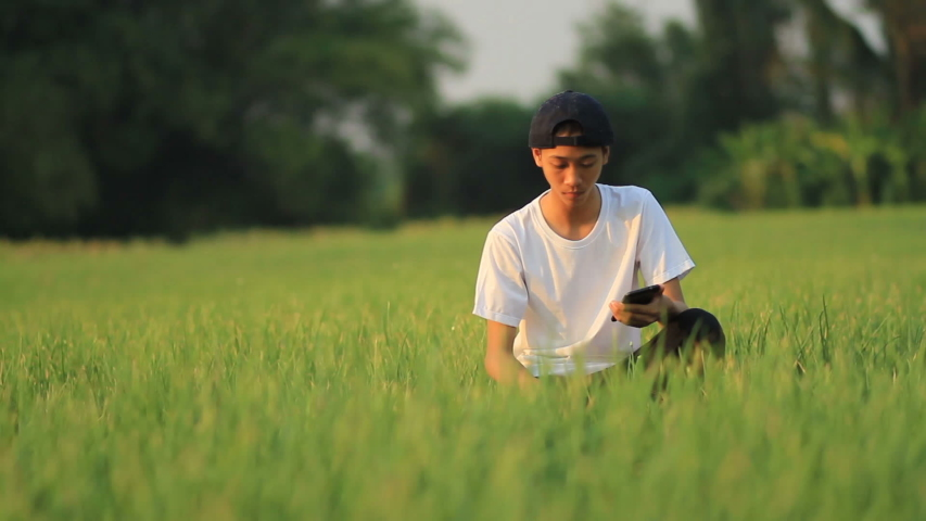 Young man learning agriculture with mobile phone at green organic onion farm, Outdoor Education and Part time job concept. | Shutterstock HD Video #1035262031
