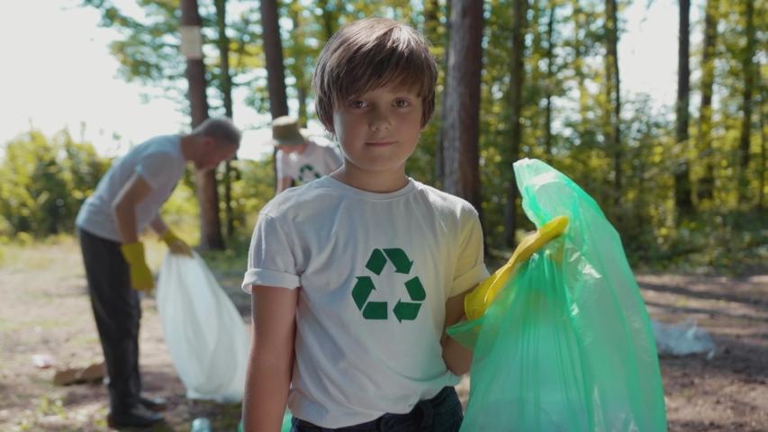 Cute boy voluteers activists child in gloves tidying up rubbish in park or forest look at camera smile | Shutterstock HD Video #1035318251