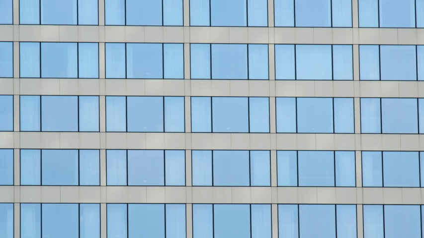 Tilt shot of modern high-rise office building with a glass facade.  | Shutterstock HD Video #1035340451