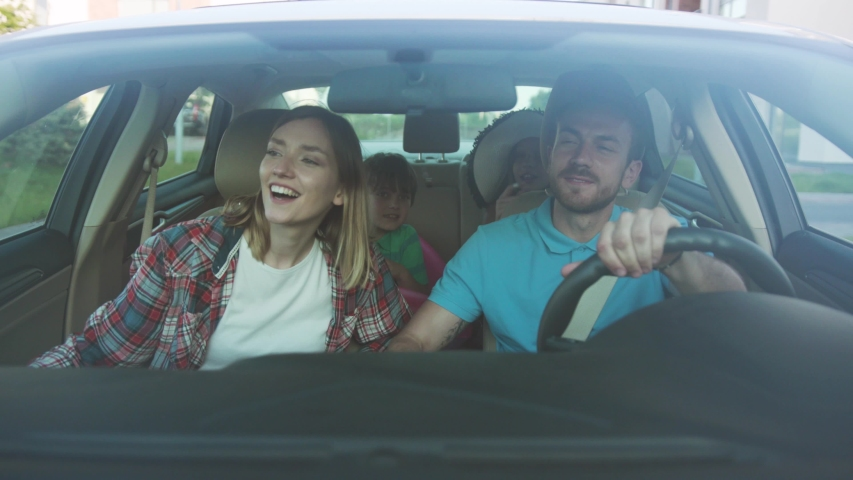 NEW YORK - June 10, 2018: Front view of happy loving parents and their excited kids smiling driving a car in the city. Young family traveling abroad by car in summer. | Shutterstock HD Video #1035354821