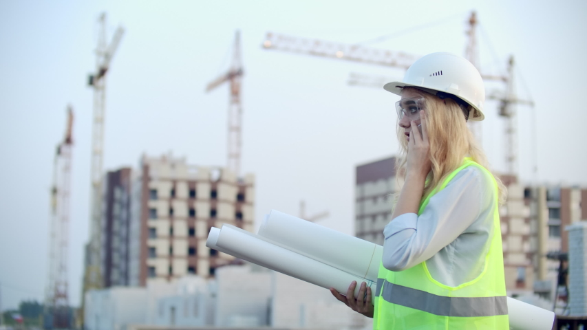 Dialogue on the phone a woman in a helmet on the background of construction discusses with the Director of the construction site of the building | Shutterstock HD Video #1035360401