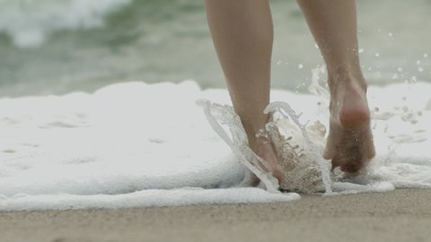 Bare female feet stepping in sea water on sandy beach close up slow motion. Faceless woman walking on coastline ocean barefoot  splashes white foam background. Health care flatfoot fungus medicine