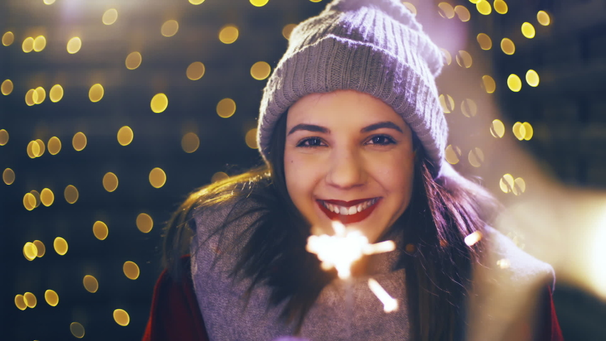 Girl with a sparkler enjoying time for Christmas. Portrait sliding shot of young woman in focus wearing winter clothes and surrounded by decorative lights. | Shutterstock HD Video #1035428441