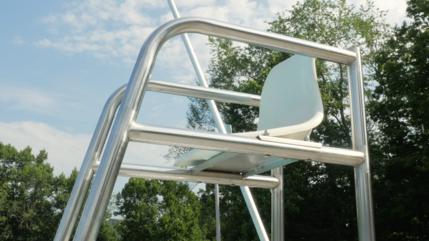 Empty lifeguard tower represents budget cuts and staffing issues. Nobody is sitting in the lifeguarding chair at a public swimming pool. Low angle represents no lifeguard on duty, and safety issues.   Shutterstock HD Video #1035486191
