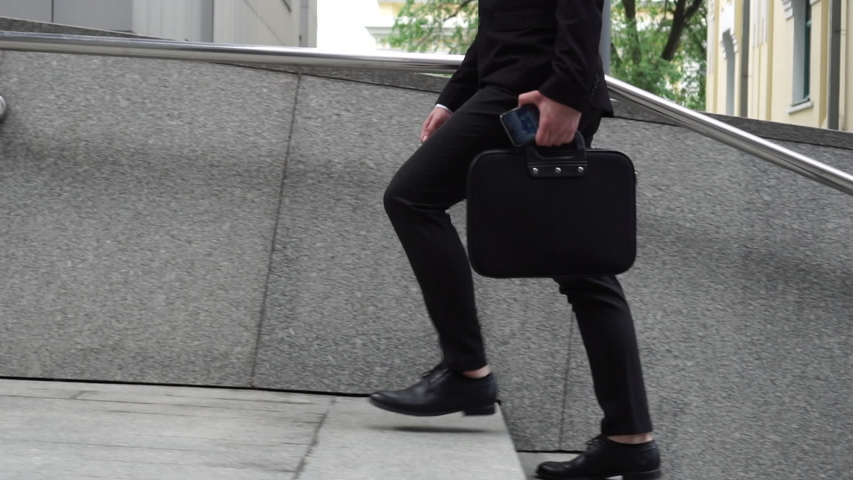 A Young Handsome Businessman Walking Up the Stairs In the Suit, with a Briefcase. Concept: a new business, communication, technology | Shutterstock HD Video #1035514991