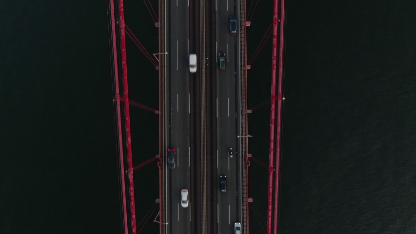 Aerial drone zoom in cars driving on The 25 April Bridge in Lisbon city, Portugal  | Shutterstock HD Video #1035518531