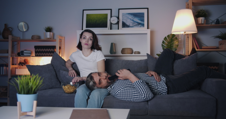 Girl and guy couple are watching TV at night eating crisps on couch together relaxing in dark room. Entertainment, rest and modern young people concept. | Shutterstock HD Video #1035520451