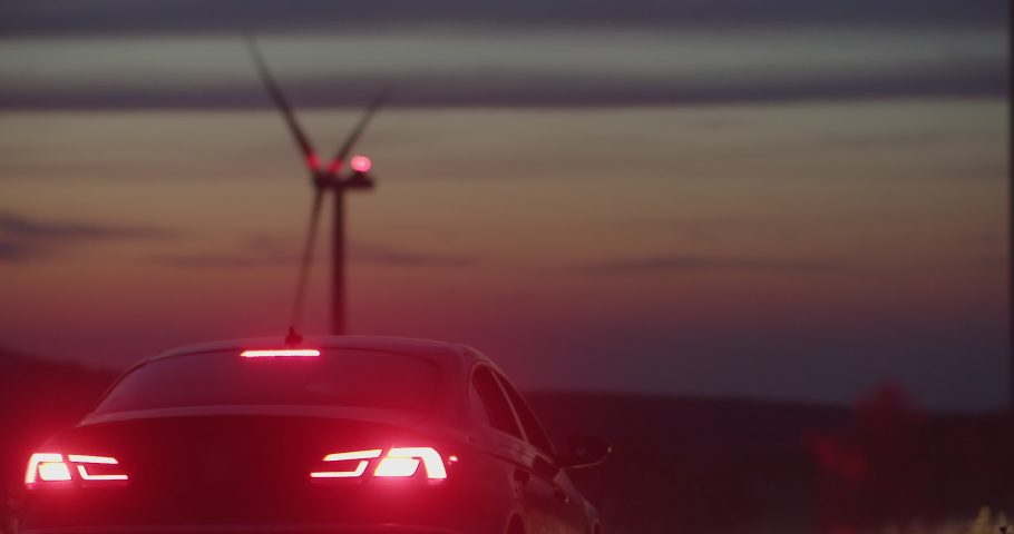 Modern car arriving to the windpower large eco-friendly station with windmills generating power spinning blades. Night time.   Shutterstock HD Video #1035557441