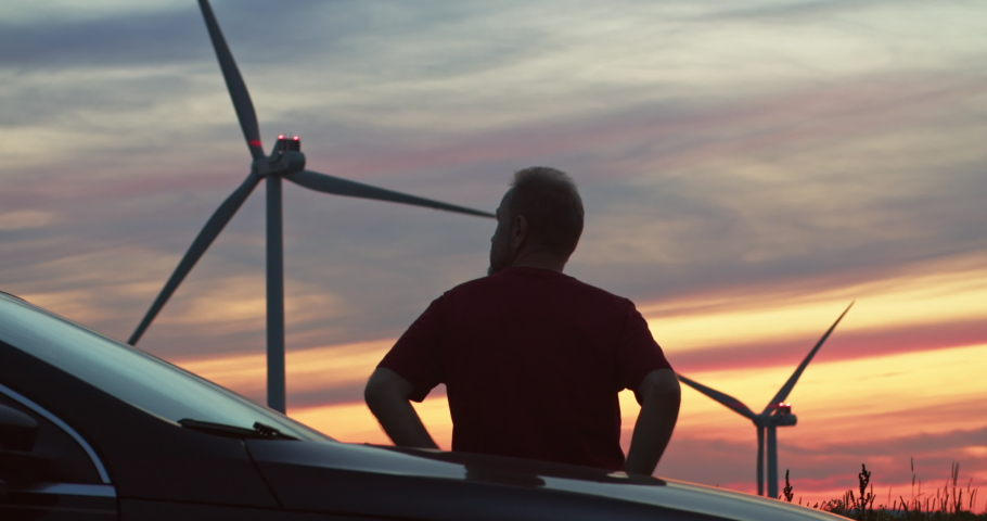 Back of inspired man enjoying scenic rural landscape with wind turbines at pink sunset. Tourist staying in windpower station alternative energy generating electricity.   Shutterstock HD Video #1035557591