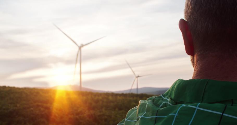 Close-up inspired man enjoying sunset sky at wind power station. Handsome farmer watching summer landscape in farmland. Environmental engineering.   Shutterstock HD Video #1035557621