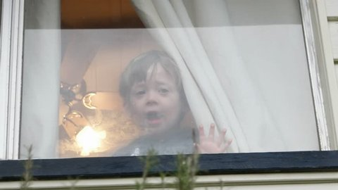 small boy making faces at window