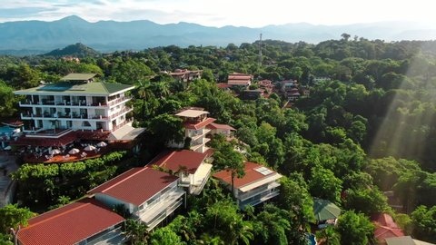 Drone Footage of Hotels and Buildings in Manuel Antonio, Costa Rica Surrounded by Green Tropical Trees with Shining Sun Flare and Mountains in the Background