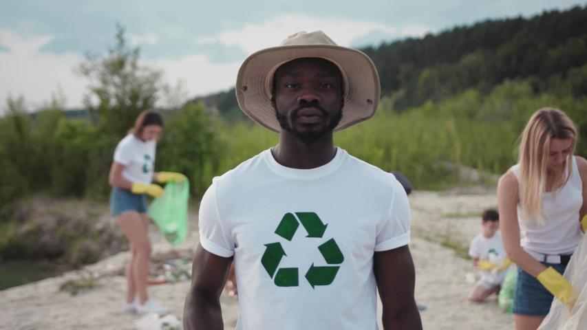 Portrait of afro-amercan ecology volunteer collecting garbage in plastic bags cleaning the beach up conducting a save environment program on the lake. Environmental moveme | Shutterstock HD Video #1035620081