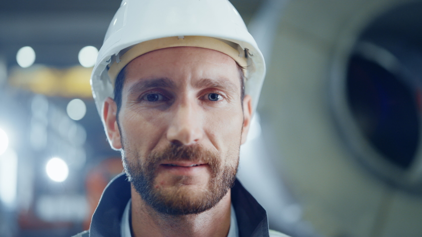 Portrait of Smiling Professional Heavy Industry Engineer / Worker Wearing Safety Uniform and Hard Hat. In the Background Unfocused Large Industrial Factory | Shutterstock HD Video #1035704021