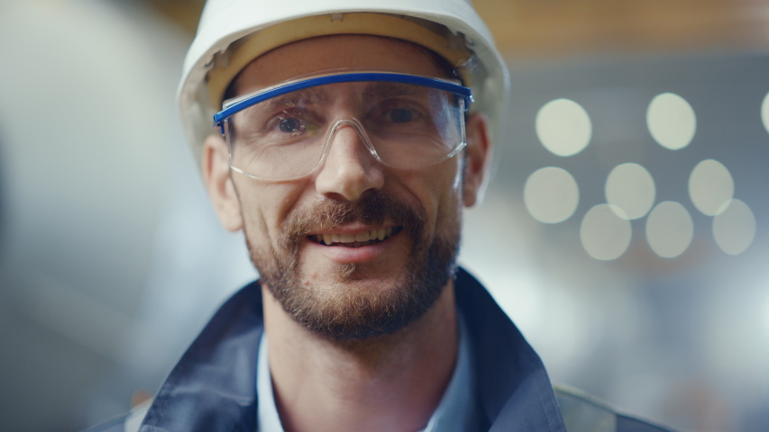 Portrait of Professional Heavy Industry Engineer / Worker Wearing Safety Uniform, Goggles and Hard Hat Smiling. In the Background Unfocused Large Industrial Factory where Welding Sparks Flying | Shutterstock HD Video #1035704111