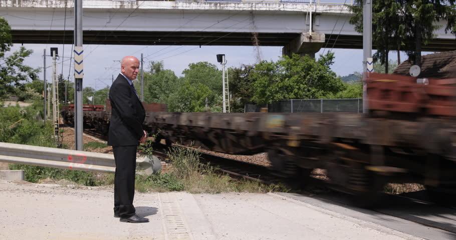 Business Man Passenger Wait Commuter Movement Cargo Train Passing Rural Station ( Ultra High Definition, UltraHD, Ultra HD, UHD, 4K, 2160P, 4096x2160 ) | Shutterstock HD Video #10357511
