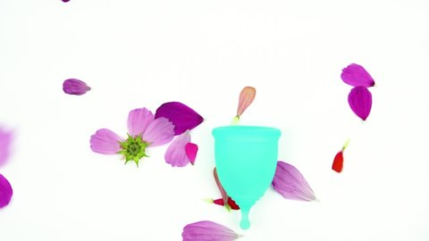 the flower petals fall unevenly on the blue menstrual cup