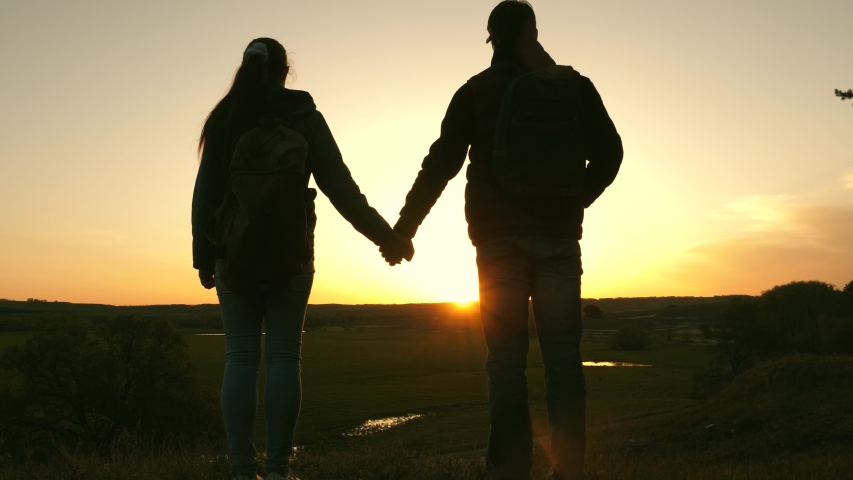 Travelers man and woman hold each other's hands and enjoy scenery at sunset. Lovers travelers travel with backpacks. Hiker Girl. Happy family of tourists on vacation travels. Romantic relationship. #1035949331