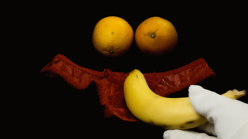 A hand in a white glove moving a banana on a women's slip and a pair of oranges. Visual metaphor for a type of sexual intercourse: use it when you must visually show but you can't put the real thing.